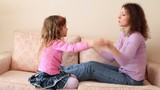Mother and daughter sit on sofa and play hands pat-a-cake game