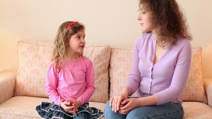 girl sits on sofa with mother and tells her about something