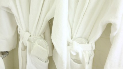 Two soft white bathrobes hang on hanger