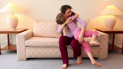 Little girl runs to mother sit on sofa at room
