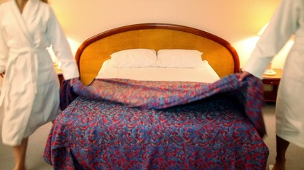 Man with woman come to bedroom and put off coverlet from bed