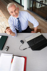 Cheerful senior businessman sitting at his desk