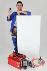 handyman with many tools showing a cell phone