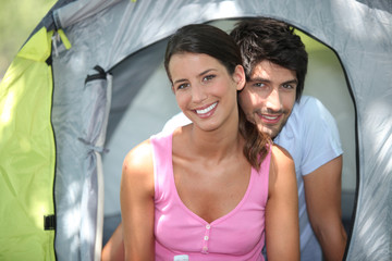 Couple sat by entrance to tent