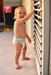 Baby standing up next to window blinds