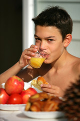 Young boy drinking orange juice in the garden