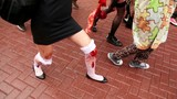 Girls zombies walk by pavement and carry bloody baby