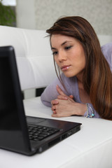 Serious woman using a laptop on a sofa