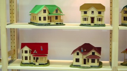 Many models of houses on wooden shelves