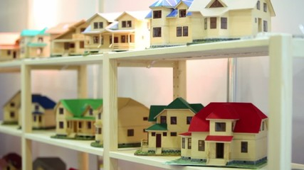 Lot of models of houses on wooden shelves