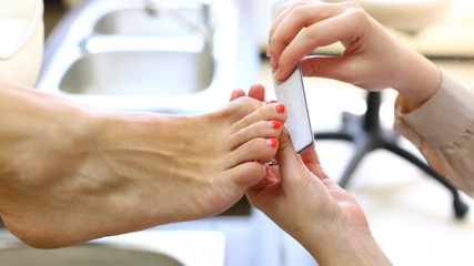 Beautician adjusts form of fingernails of woman