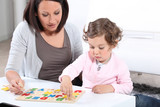 Mother and daughter completing a letter puzzle