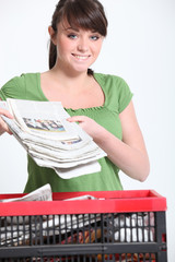 Woman recycling newspaper