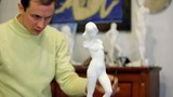 Sculptor polishes figurine at background of other statuettes