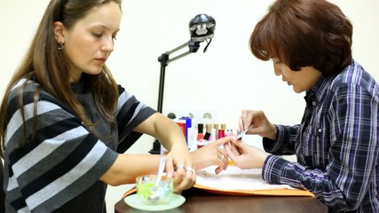 Manicure technician does manicure for client