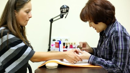 Manicure technician talks to client and does to she manicure