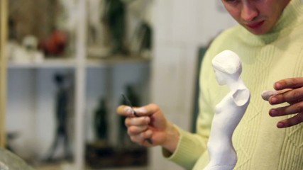 Sculptor holds armless female figurine and corrects it