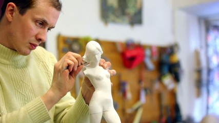 Sculptor corrects armless female figurine by file