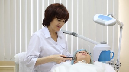 Beautician does galvanotherapy on face to client