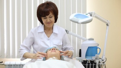 Woman receives facial massage in beauty shop from beautician