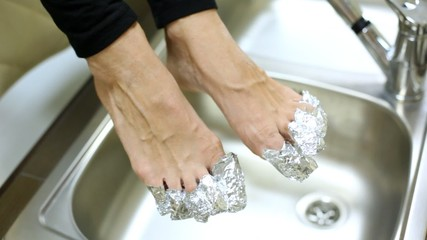 Woman fingers wrap up in foil to make correction of nails