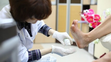 Cosmetician does pedicure, rubs cosmetic oil in foot