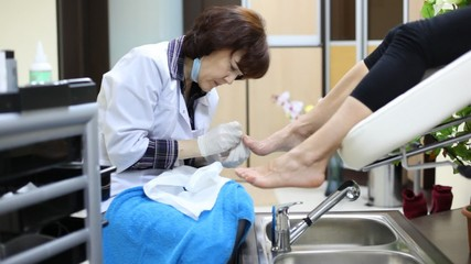 Cosmetician does pedicure to woman and has spread on towel