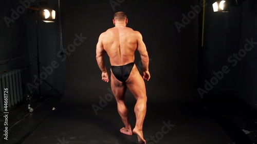 Bodybuilder shows his muscular body in dark studio