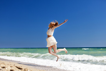 Young redhead girl jumping at the beach.