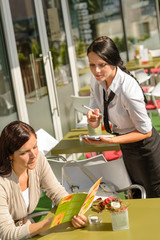 Waitress waiting for woman to order menu