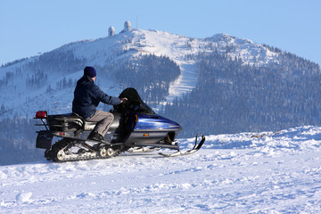 Man riding on the snowmobile.