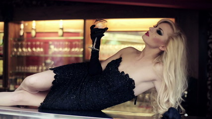 Gorgeous blonde woman lying on bar counter with wine