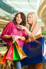 Two women shopping with bags in mall