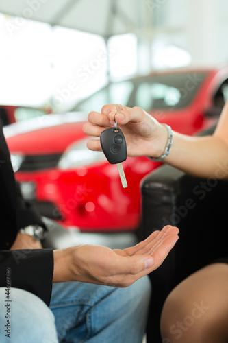Frau übergibt Mann Autoschlüssel