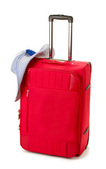 Red suitcase with woman's hat isolated on white