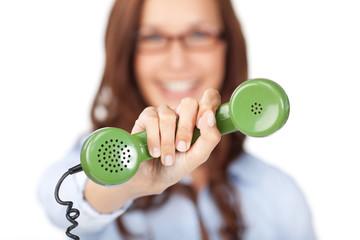 lächelnde frau zeigt grünen telefonhörer