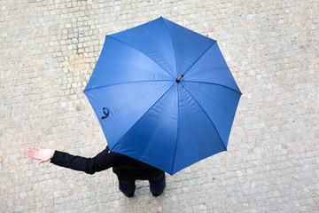 Business man hidden under umbrella and checking if it's raining