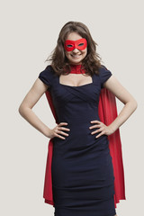 Portrait of a young woman in superhero costume over gray background