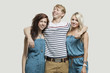 Portrait of two young women in similar jumpsuits standing with happy male friend over gray background