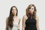Portrait of young women blowing party puffers against gray background