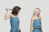 Friend stabbing young woman in similar jump suits from behind
