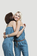 Two young female friends in matching jump suits hugging each other over gray background