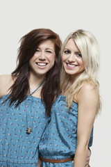 Portrait of two young women in similar jump suits smiling over gray background