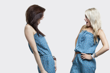 Two shocked women wearing matching jump suits looking at each other over gray background