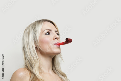 Young woman with party blower looking away over gray background
