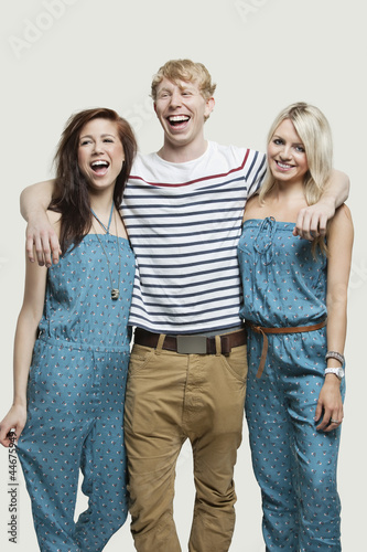 Portrait of young woman standing with cheerful friends against gray background