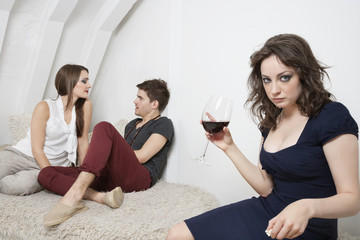 Portrait of an irritated young woman holding wine glass with couple in the background