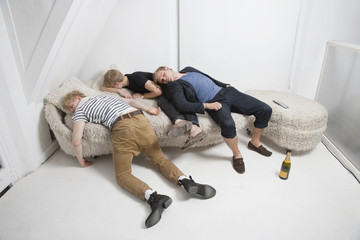 Drunk male friends sleeping on fur sofa after party