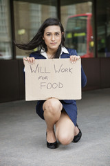 Young Indian businesswoman holding 'Will Work for Food' sign