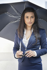 Portrait of a young Indian businesswoman holding umbrella
